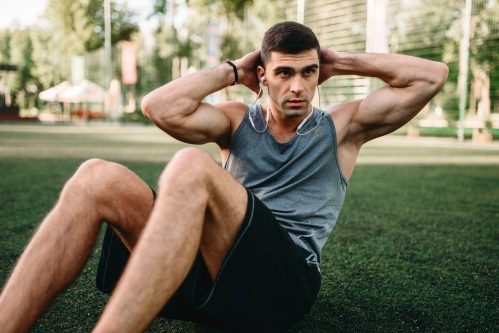 man exercising on grass